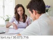 Купить «Young couple sitting with home bills at table», фото № 30073716, снято 12 декабря 2013 г. (c) Wavebreak Media / Фотобанк Лори