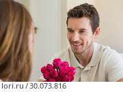 Купить «Happy man looking at woman with flowers», фото № 30073816, снято 12 декабря 2013 г. (c) Wavebreak Media / Фотобанк Лори