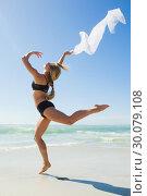 Купить «Fit blonde jumping gracefully with scarf on the beach», фото № 30079108, снято 14 февраля 2014 г. (c) Wavebreak Media / Фотобанк Лори