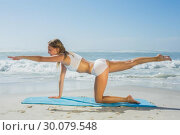 Gorgeous fit blonde in pilates pose on the beach. Стоковое фото, агентство Wavebreak Media / Фотобанк Лори