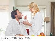 Купить «Cute couple in bathrobes having breakfast together», фото № 30079736, снято 24 января 2014 г. (c) Wavebreak Media / Фотобанк Лори