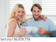 Купить «Smiling casual couple sitting on couch having coffee», фото № 30079776, снято 24 января 2014 г. (c) Wavebreak Media / Фотобанк Лори