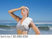 Купить «Sporty blonde standing on the beach with towel», фото № 30080656, снято 12 февраля 2014 г. (c) Wavebreak Media / Фотобанк Лори