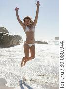 Купить «Beautiful smiling woman in white bikini leaping on the beach», фото № 30080944, снято 12 февраля 2014 г. (c) Wavebreak Media / Фотобанк Лори