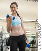 Купить «Fit smiling brunette lifting blue dumbbells», фото № 30081304, снято 26 февраля 2014 г. (c) Wavebreak Media / Фотобанк Лори