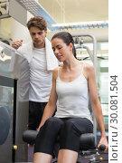 Купить «Fit brunette using weights machine for legs with trainer watching», фото № 30081504, снято 26 февраля 2014 г. (c) Wavebreak Media / Фотобанк Лори