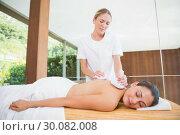 Купить «Smiling woman getting a back massage with herbal compresses», фото № 30082008, снято 9 апреля 2014 г. (c) Wavebreak Media / Фотобанк Лори