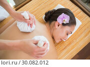 Купить «Smiling woman getting a back massage with herbal compresses», фото № 30082012, снято 9 апреля 2014 г. (c) Wavebreak Media / Фотобанк Лори