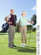Купить «Golfing couple standing and looking around», фото № 30082108, снято 3 апреля 2014 г. (c) Wavebreak Media / Фотобанк Лори