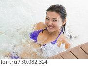 Купить «Smiling brunette in bikini relaxing in hot tub», фото № 30082324, снято 8 апреля 2014 г. (c) Wavebreak Media / Фотобанк Лори