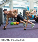 Купить «Bodybuilding man and woman lifting kettlebells in plank position», фото № 30082608, снято 2 апреля 2014 г. (c) Wavebreak Media / Фотобанк Лори
