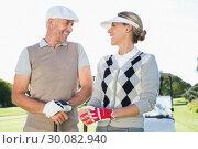 Купить «Happy golfing couple facing each other with golf buggy behind», фото № 30082940, снято 3 апреля 2014 г. (c) Wavebreak Media / Фотобанк Лори