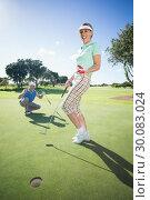 Купить «Golfing couple cheering on the putting green», фото № 30083024, снято 3 апреля 2014 г. (c) Wavebreak Media / Фотобанк Лори