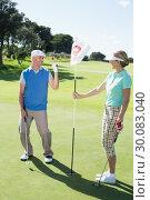Купить «Lady golfer holding eighteenth hole flag for cheering partner», фото № 30083040, снято 3 апреля 2014 г. (c) Wavebreak Media / Фотобанк Лори