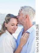 Купить «Man kissing his smiling partner on the forehead at the beach», фото № 30083268, снято 3 апреля 2014 г. (c) Wavebreak Media / Фотобанк Лори