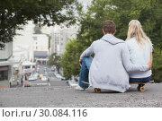 Купить «Cute young couple sitting on skateboard », фото № 30084116, снято 19 февраля 2014 г. (c) Wavebreak Media / Фотобанк Лори