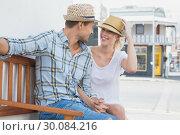 Купить «Young hip couple sitting on bench smiling at each other», фото № 30084216, снято 19 февраля 2014 г. (c) Wavebreak Media / Фотобанк Лори