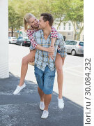 Купить «Young hip man giving his blonde girlfriend a piggy back», фото № 30084232, снято 19 февраля 2014 г. (c) Wavebreak Media / Фотобанк Лори