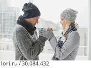 Купить «Cute couple in warm clothing smiling at each other», фото № 30084432, снято 19 февраля 2014 г. (c) Wavebreak Media / Фотобанк Лори