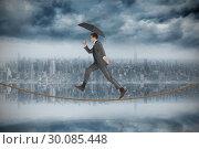 Купить «Composite image of businessman jumping holding an umbrella on tightrope», фото № 30085448, снято 11 июня 2014 г. (c) Wavebreak Media / Фотобанк Лори