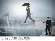 Купить «Young business man pulling a tightrope for businessman», фото № 30086036, снято 11 июня 2014 г. (c) Wavebreak Media / Фотобанк Лори
