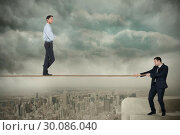 Купить «Young business man pulling a tightrope for businessman», фото № 30086040, снято 11 июня 2014 г. (c) Wavebreak Media / Фотобанк Лори