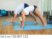 Купить «Sporty couple in bending posture at fitness studio», фото № 30087132, снято 27 февраля 2014 г. (c) Wavebreak Media / Фотобанк Лори