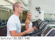 Купить «Side view of couple running on treadmills at gym», фото № 30087148, снято 27 февраля 2014 г. (c) Wavebreak Media / Фотобанк Лори