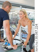 Купить «Smiling fit couple working on exercise bikes at gym», фото № 30087224, снято 27 февраля 2014 г. (c) Wavebreak Media / Фотобанк Лори