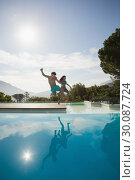 Купить «Cheerful couple jumping into swimming pool», фото № 30087724, снято 8 апреля 2014 г. (c) Wavebreak Media / Фотобанк Лори