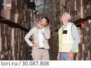 Купить «Pretty warehouse manager talking to foreman», фото № 30087808, снято 10 мая 2014 г. (c) Wavebreak Media / Фотобанк Лори