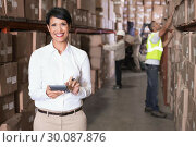 Купить «Pretty warehouse manager using calculator», фото № 30087876, снято 10 мая 2014 г. (c) Wavebreak Media / Фотобанк Лори