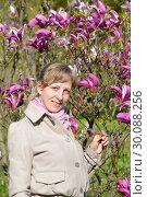 Купить «Молодая женщина стоит около цветущей магнолии лилиецветной», фото № 30088256, снято 3 мая 2016 г. (c) Ирина Борсученко / Фотобанк Лори