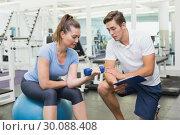 Купить «Personal trainer working with client holding dumbbell», фото № 30088408, снято 5 марта 2014 г. (c) Wavebreak Media / Фотобанк Лори