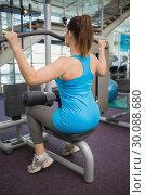 Купить «Fit brunette using weights machine for arms», фото № 30088680, снято 5 марта 2014 г. (c) Wavebreak Media / Фотобанк Лори