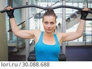 Купить «Fit brunette using weights machine for arms», фото № 30088688, снято 5 марта 2014 г. (c) Wavebreak Media / Фотобанк Лори