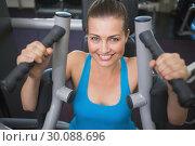 Купить «Fit brunette using weights machine for arms», фото № 30088696, снято 5 марта 2014 г. (c) Wavebreak Media / Фотобанк Лори