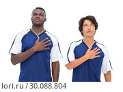 Football players in blue listening to anthem. Стоковое фото, агентство Wavebreak Media / Фотобанк Лори