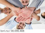 Купить «Four workers stacking hands together», фото № 30090408, снято 6 мая 2014 г. (c) Wavebreak Media / Фотобанк Лори