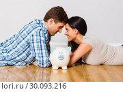 Купить «Young couple lying on floor smiling with piggy bank», фото № 30093216, снято 2 июля 2014 г. (c) Wavebreak Media / Фотобанк Лори