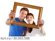 Купить «Couple holding frame ahead of them», фото № 30093588, снято 4 июля 2014 г. (c) Wavebreak Media / Фотобанк Лори