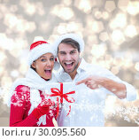 Купить «Composite image of festive young couple holding gift», фото № 30095560, снято 28 августа 2014 г. (c) Wavebreak Media / Фотобанк Лори