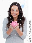 Купить «Composite image of smiling woman looking at piggy bank in her hands», фото № 30096408, снято 29 августа 2014 г. (c) Wavebreak Media / Фотобанк Лори