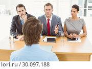 Business people interviewing man in office. Стоковое фото, агентство Wavebreak Media / Фотобанк Лори