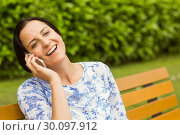 Smiling brunette sitting on bench phoning. Стоковое фото, агентство Wavebreak Media / Фотобанк Лори