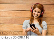 Купить «Girl listening music with headphones while sending message», фото № 30098116, снято 13 июня 2014 г. (c) Wavebreak Media / Фотобанк Лори