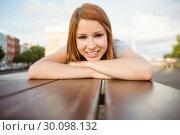 Купить «Portrait of a smiling redhead lying on bench», фото № 30098132, снято 13 июня 2014 г. (c) Wavebreak Media / Фотобанк Лори