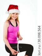 Купить «Fit festive young blonde measuring her thigh», фото № 30098564, снято 18 июля 2014 г. (c) Wavebreak Media / Фотобанк Лори