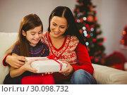 Купить «Festive mother and daughter holding christmas present», фото № 30098732, снято 24 июля 2014 г. (c) Wavebreak Media / Фотобанк Лори