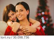 Купить «Festive mother and daughter smiling at camera», фото № 30098736, снято 24 июля 2014 г. (c) Wavebreak Media / Фотобанк Лори